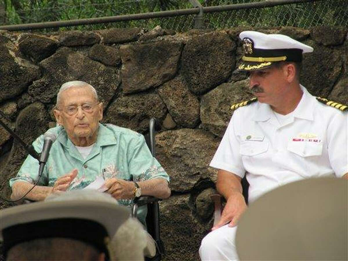 Retired Rear Adm. Mac Showers, left, the last surviving member of the intelligence team that deciphered Japanese messages in the lead up to the Battle of Midway, speaks during a ceremony Friday in Pearl Harbor, Hawaii. Listening at right is Capt. James Fannell, the Pacific Fleet's deputy chief of staff for intelligence. Showers and Navy officials are observing Monday the 70th anniversary of the battle that changed the course of World War II. Associated Press