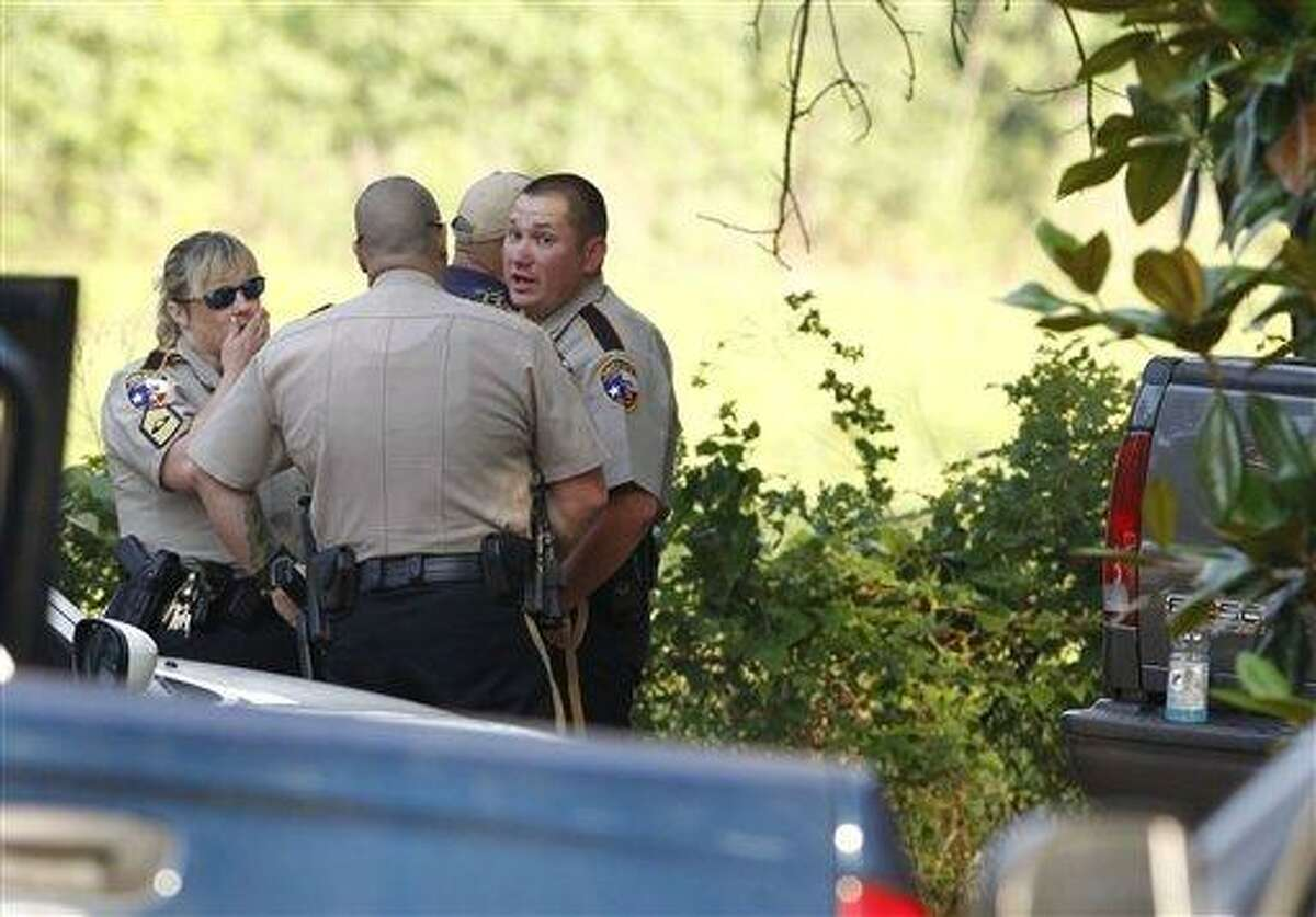 Law enforcement officials are on the scene of a home in Hardin, Texas Tuesday, June 7, 2011, after receiving an anonymous tip that multiple dismembered bodies were buried there. A sheriff's spokesman said officials were seeking a search warrant for the property. (AP Photo/Houston Chronicle, Nick de la Torre)