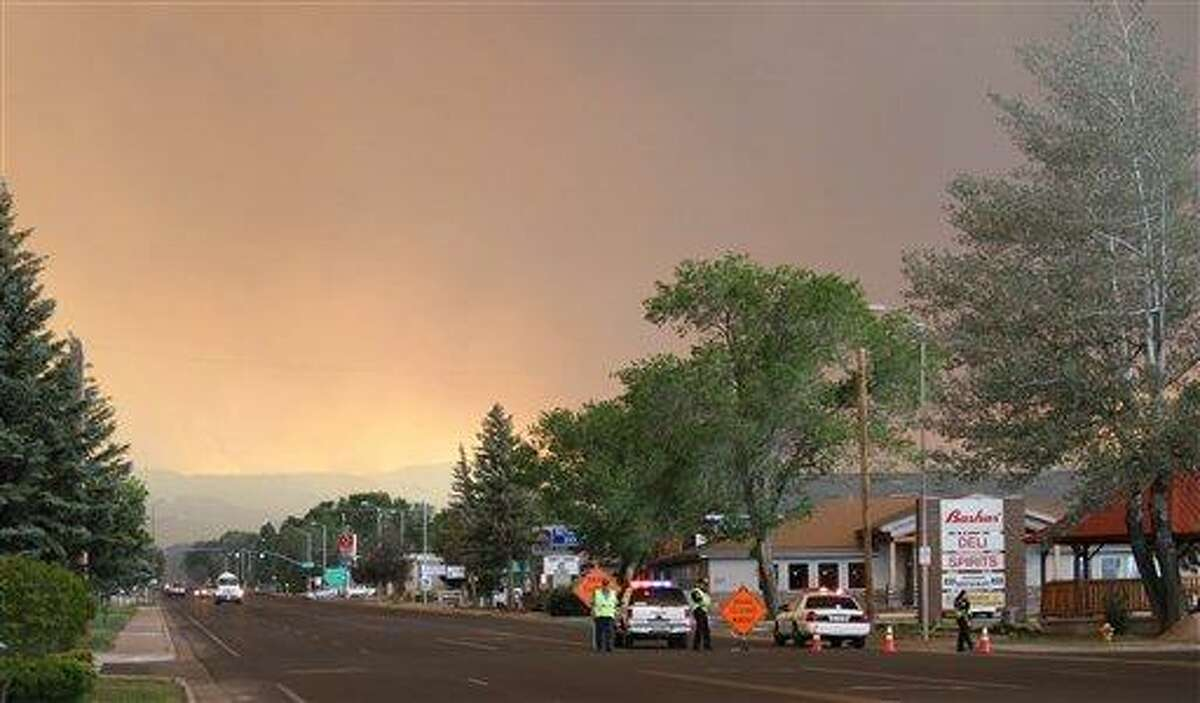 Authorities block the road heading to the southern half of Eagar, Ariz., after the Wallow Fire forced evacuations in part of the community on Tuesday, June 7, 2011. Flames from a mammoth forest fire licked the ridges surrounding the eastern Arizona town Tuesday afternoon, forcing the evacuation of about half the 4,000 residents as surrounding towns also prepared to empty. (AP Photo/Susan Montoya Bryan)