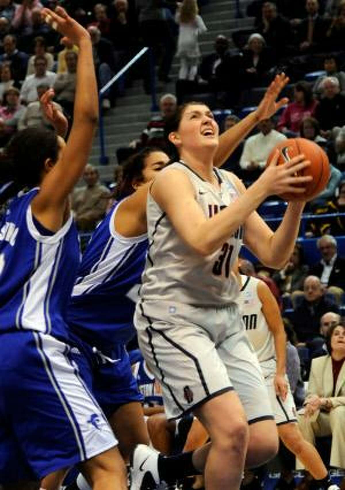 AP Connecticut's Stefanie Dolson comes in for a shot past Seton Hall defenders during the first half of Tuesday's game in Hartford. The Huskies won 80-59.
