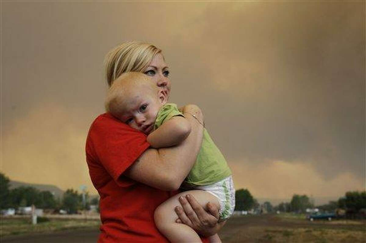 Emily Shupe comforts her 18-month-old son Jax as the family prepares to evacuate to Phoenix as the Wallow fire approaches in Springerville, Ariz., Tuesday, June 7, 2011. The blaze has burned 486 square miles of ponderosa pine forest, driven by wind gusts of more than 60 mph since it was sparked on May 29 by what authorities believe was an unattended campfire. It officially became the second-largest in Arizona history on Tuesday. (AP Photo/Marcio Jose Sanchez)