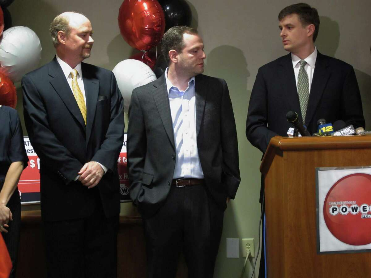 From left, Tim Davidson, Brandon Lacoff and Greg Skidmore, three asset managers from Greenwich, claim a $254 million Powerball prize Monday at Connecticut Lottery headquarters in Rocky Hill. (AP Photo/Pat Eaton-Robb)