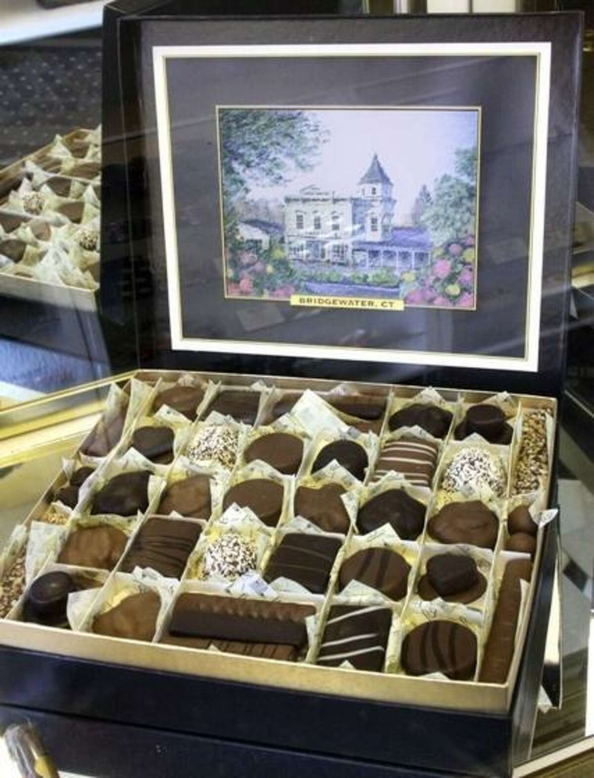 A large gift box of Bridgewater Chocolates features an image of the Bridgewater Village Store, the charming hub of a small town where the business was born. The chocolates are now made in a headquarters in Brookfield.