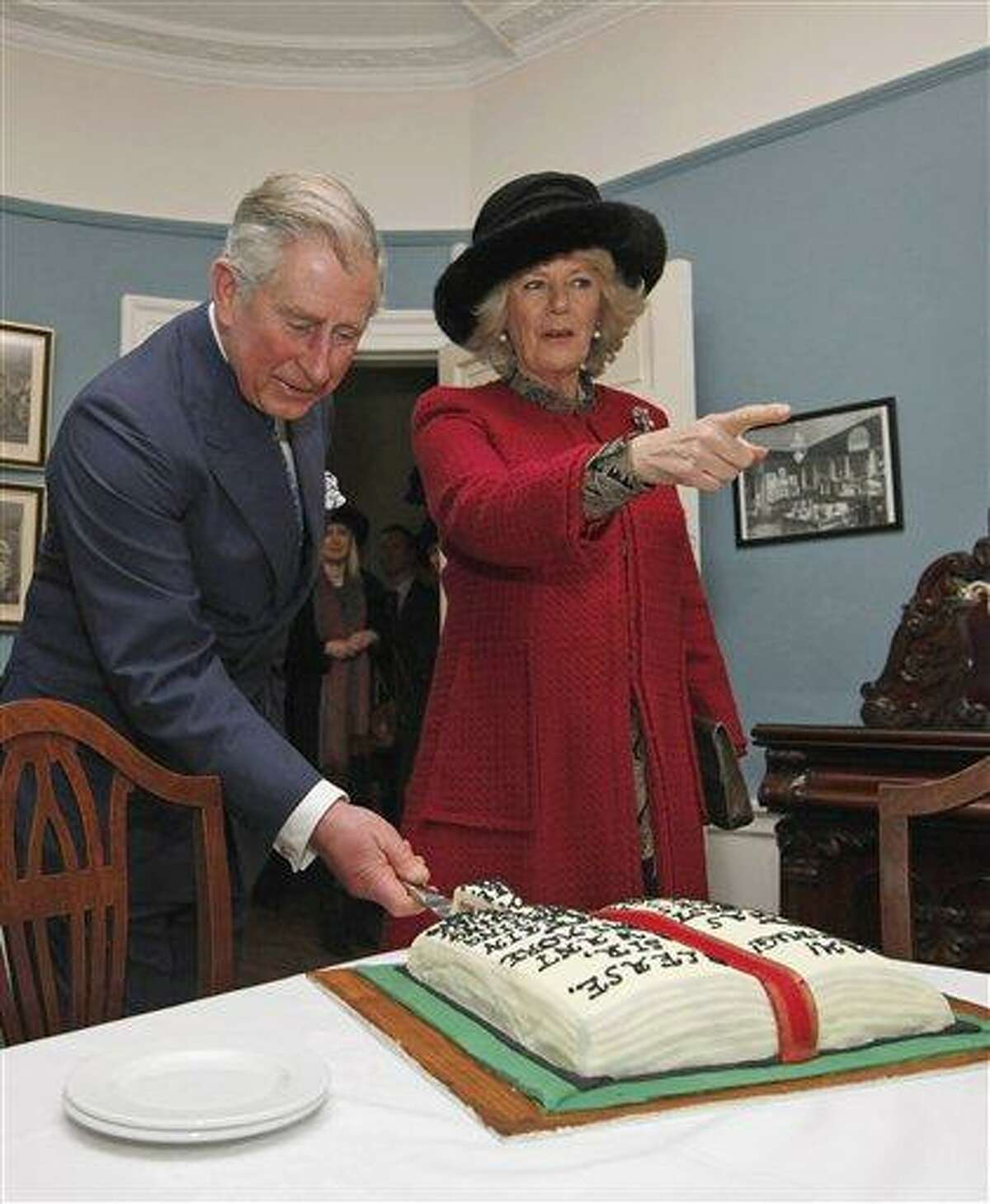 Britain's Prince Charles cuts a birthday cake in honor of Charles Dickens as he stands with his wife Camilla, Duchess of Cornwall, right, at the Dickens Museum in London Tuesday. Associated Press