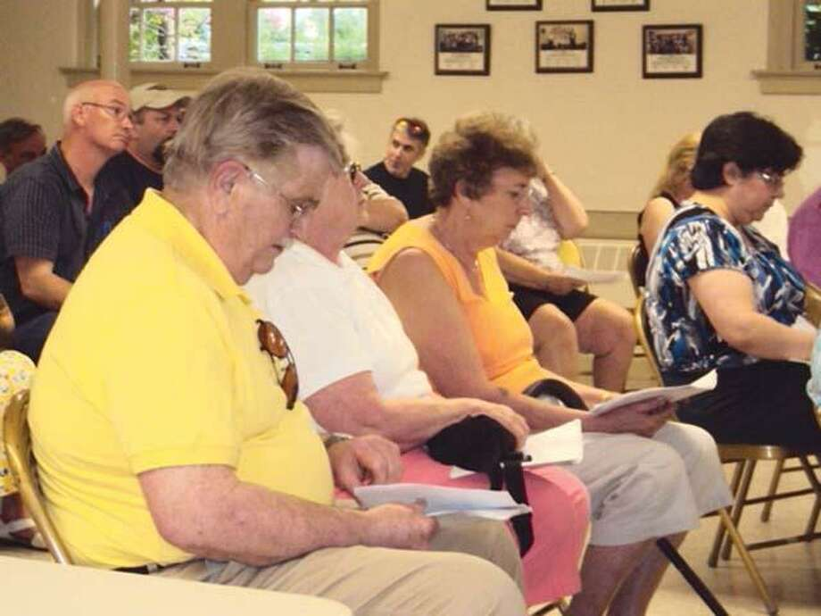 RICKY CAMPBELL/ Register CitizenVoters in Morris flip through the budget hand out during Wednesday's town meeting. The residents voted unanimously to approve the budget for 2011-12.