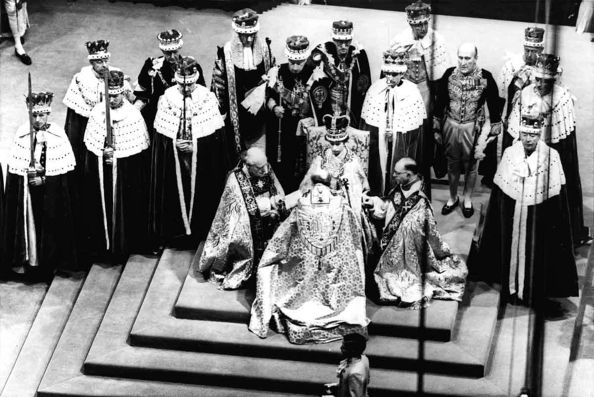 In this June 2, 1953 file photo, Britain's Queen Elizabeth II, seated on the throne, receives the fealty of the Archbishop of Canterbury, back to camera at center, the Bishop of Durham, left and the Bishop of Bath and Wells, during her coronation in Westminster Abbey, London. Associated Press file photo