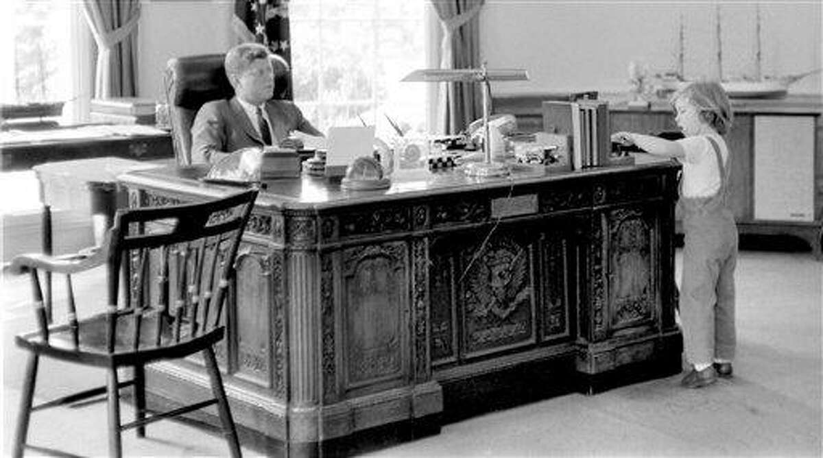 This May 16, 1962 photograph released by the John F. Kennedy Presidential Library and Museum in Boston shows President John F. Kennedy behind his desk while visited by his daughter Caroline in the Oval Office at the White House in Washington. On Monday, Feb. 21, 2011, Caroline Kennedy will unveil a new feature at the museum where anyone can use the Internet to ?sit? at the virtual desk to learn more about her father's life and administration. (AP Photo/John F. Kennedy Presidential Library and Museum, Robert Knudsen)