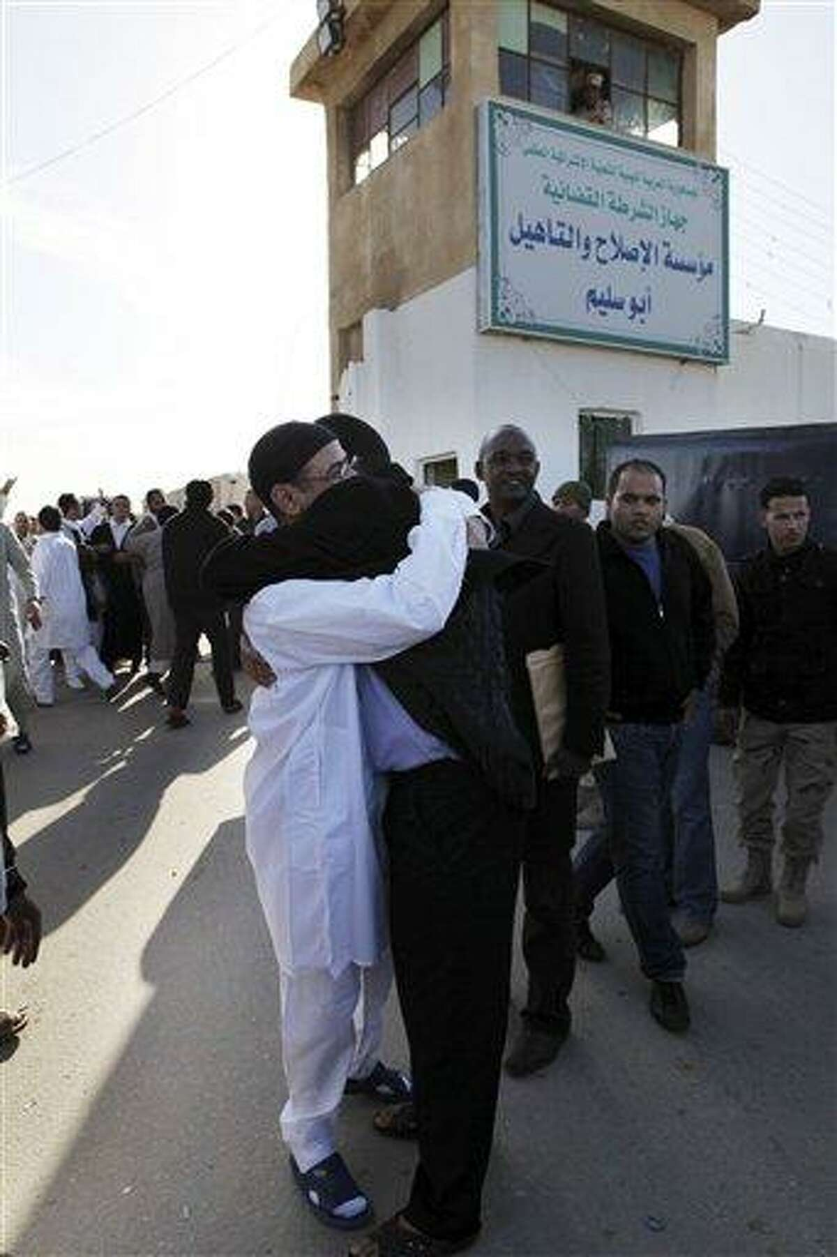 A Libyan prisoner, left, is hugged by his relatives after he was released with a group of 110 prisoners from Abu Salim, Libya's most notorious prison, in Tripoli, Libya, Wednesday, Feb. 16, 2011. Egypt-inspired unrest spread against Libya's longtime ruler Moammar Gadhafi on Wednesday, with riot police clashing with protesters in the second-largest city of Benghazi and marchers setting fire to security headquarters and a police station in the city of Zentan, witnesses said. Gadhafi's government sought to allay further unrest by proposing the doubling of government employees' salaries and releasing 110 suspected Islamic militants who oppose him tactics similar to those used by other Arab regimes in the recent wave of protests. (AP Photo/ Abdel Magid Al Fergany)