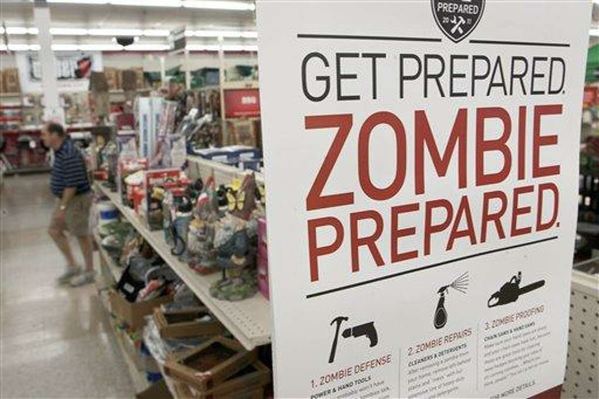 In this October 2011 file photo, a sign promoting zombie preparedness displays in a hardware store in Omaha, Neb. After several gory incidents that have been reported around the country recently, online zombie talk has grown. Associated Press
