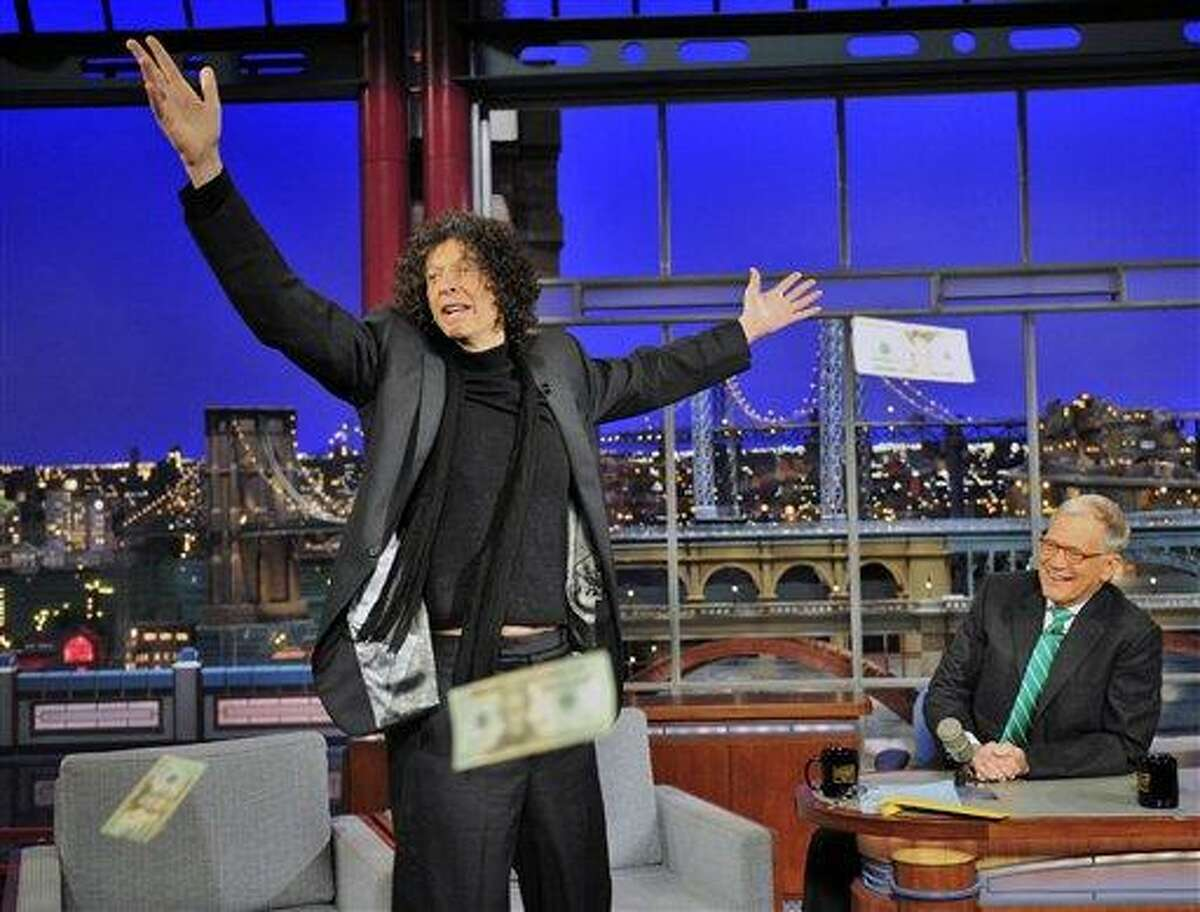 In this photo provided by CBS, Sirius radio personality Howard Stern throws money to the audience on the set of the 'Late Show with David Letterman,' Wednesday, in New York. The money was set aside by Letterman to entice actor Brad Pitt to appear on the show. (AP Photo/CBS, John Paul Filo)