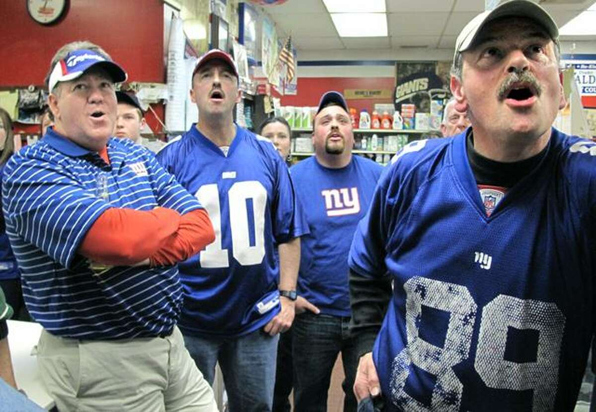 DEBBIE MORELLO/Register Citizen Tony Renzullo (right) owns Carbone's Market. He was closed for business but held a Super Bowl party for friends and family on Sunday -- all are diehard Giants fans. Tom Jacquot (far left) City Councilman Drake Waldron (2nd to left) Eric Renzullo (back) and Tony Renzullo react to a play in the first quarter.