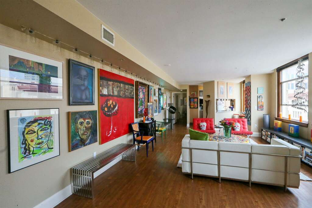 Art, Mostly By Local Artists, Fills Almost Every Inch Of A Living Room Wall