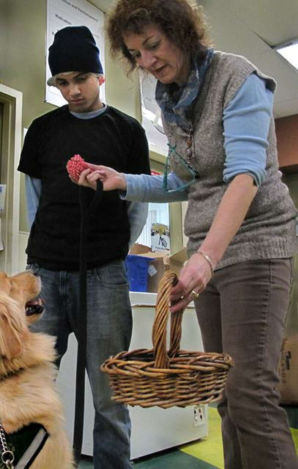Co-founder of ECAD, Lu Picard, is teaching Allen to be the best service dog he can be. She's teaching him to carry a basket. One of her students, Cesar looks on. Picard co-founded ECAD with her husband Dale in 1995.