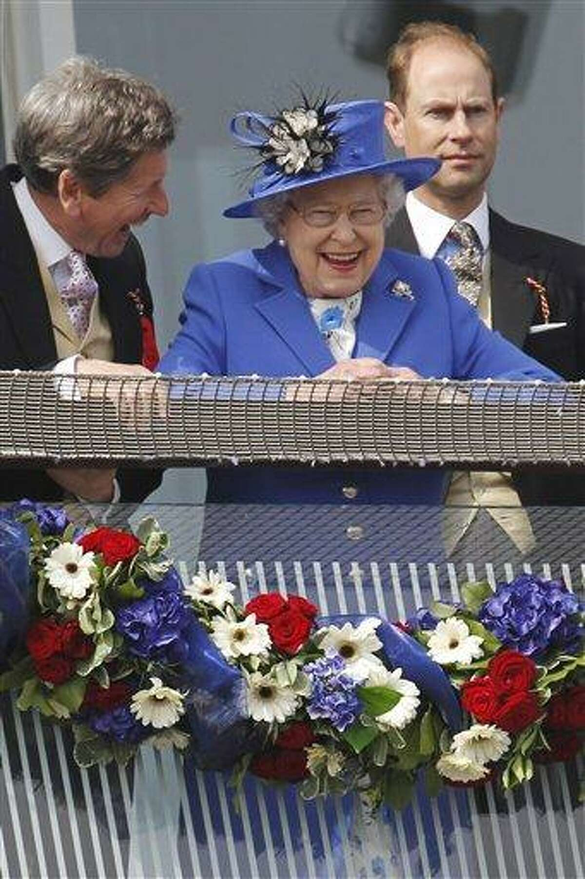 Britain's Queen Elizabeth II, center, reacts as she looks out from the balcony at the end of the Epsom Derby horse race Saturday at Epsom racecourse England at the start of a four-day Diamond Jubilee celebration to mark the 60th anniversary of her accession to the throne. Associated Press