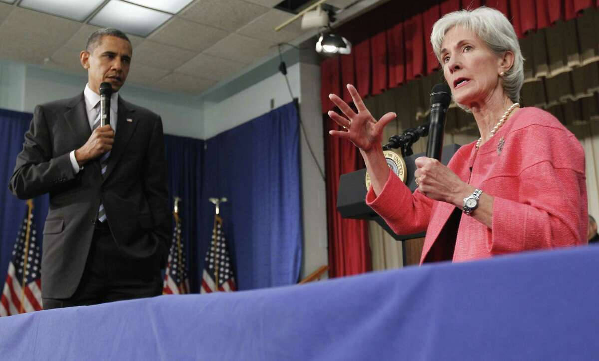 In this file photo from 2010, President Barack Obama listens as Health and Human Services Secretary Kathleen Sebelius speaks during a town hall meeting on the Affordable Care Act, at the Holiday Park Multipurpose Senior Center in Wheaton, Md. Medicare's prescription coverage gap is getting noticeably smaller and easier to manage this year for millions of older and disabled people with high drug costs. The
