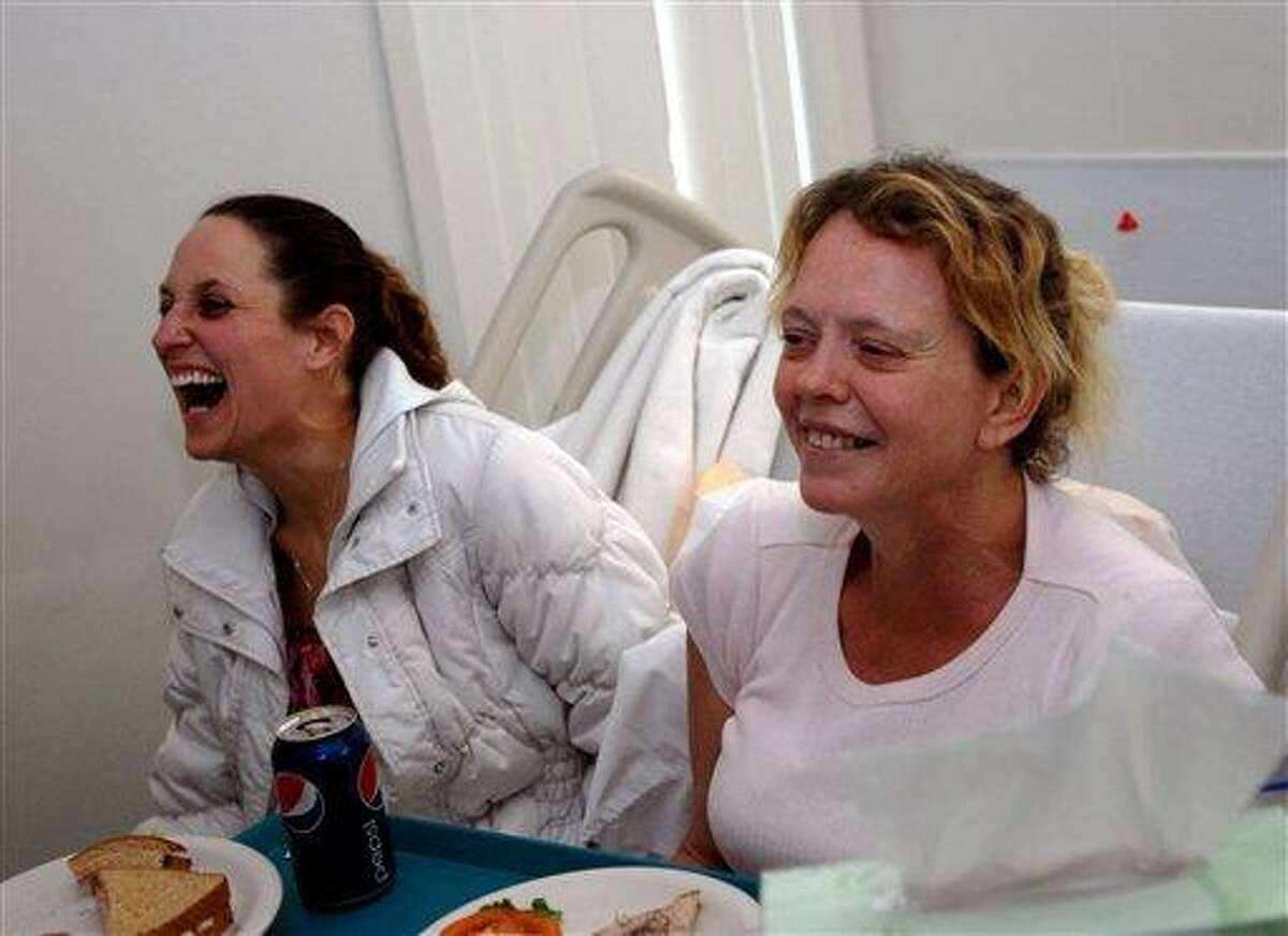 Belinda Conne, right, shares a laugh with an unidentified friend Sunday. Associated Press