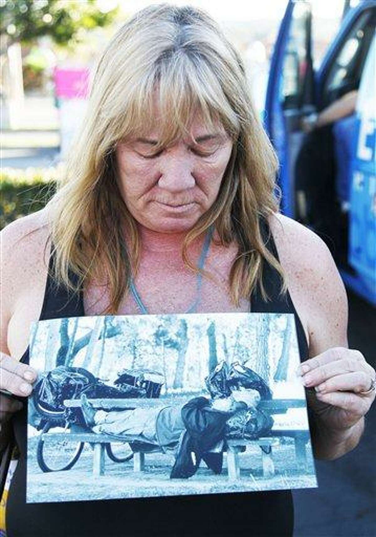 Anaheim, Calif., resident Marilyn Holland holds a photo of John Berry, 64, a Vietnam homeless veteran who was stabbed to death by a serial killer, as she pays her respects in Anaheim Wednesday. Prosecutors have charged Itzcoatl Ocampo, 23, a former Marine and a Iraq war veteran, with the murders of four homeless men in a near month-long spree that prompted police in Orange County to urge the homeless to seek shelter indoors. Associated Press