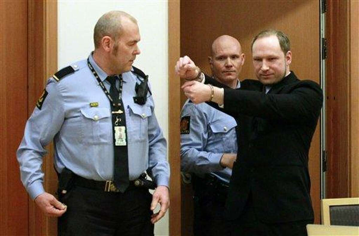 Anders Behring Breivik, right, a right-wing extremist who confessed to a bombing and mass shooting that killed 77 people on July 22, 2011, gestures as he arrives for a detention hearing at a court in Oslo, Norway, Monday. Associated Press