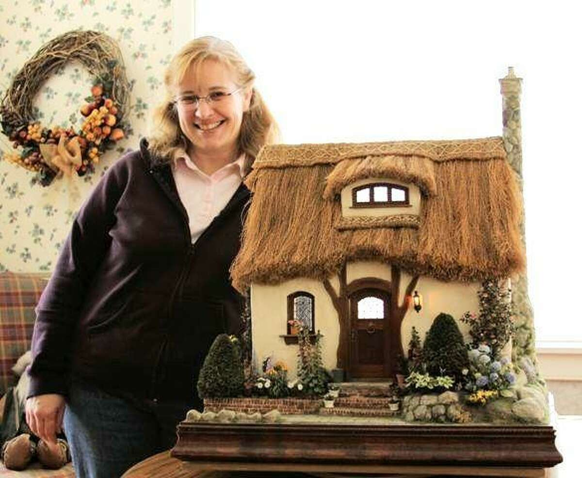 Teresa Layman at home in Warren with an English cottage doll house she created.