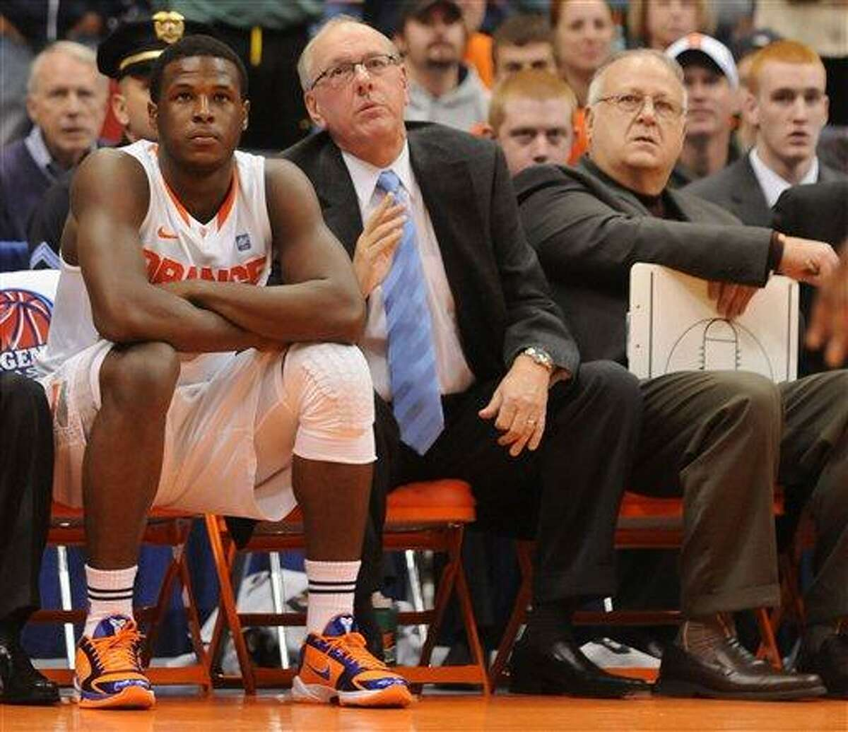 In this Nov. 21, 2010 file photo, Syracuse basketball player Dion Waiter, left, sits on the bench beside head coach Jim Boeheim, center, and assistant coach Bernie Fine, right, during a game against William & Mary, in Syracuse, N.Y. Fine was placed on administrative leave Thursday, Nov. 17, 2011 after old child molesting allegations resurfaced, just two weeks after a child sex abuse scandal rocked Penn State. (AP Photo/The Post Standard, Dennis Nett) INTERNET OUT TV OUT MAGS OUT NO ARCHIVE