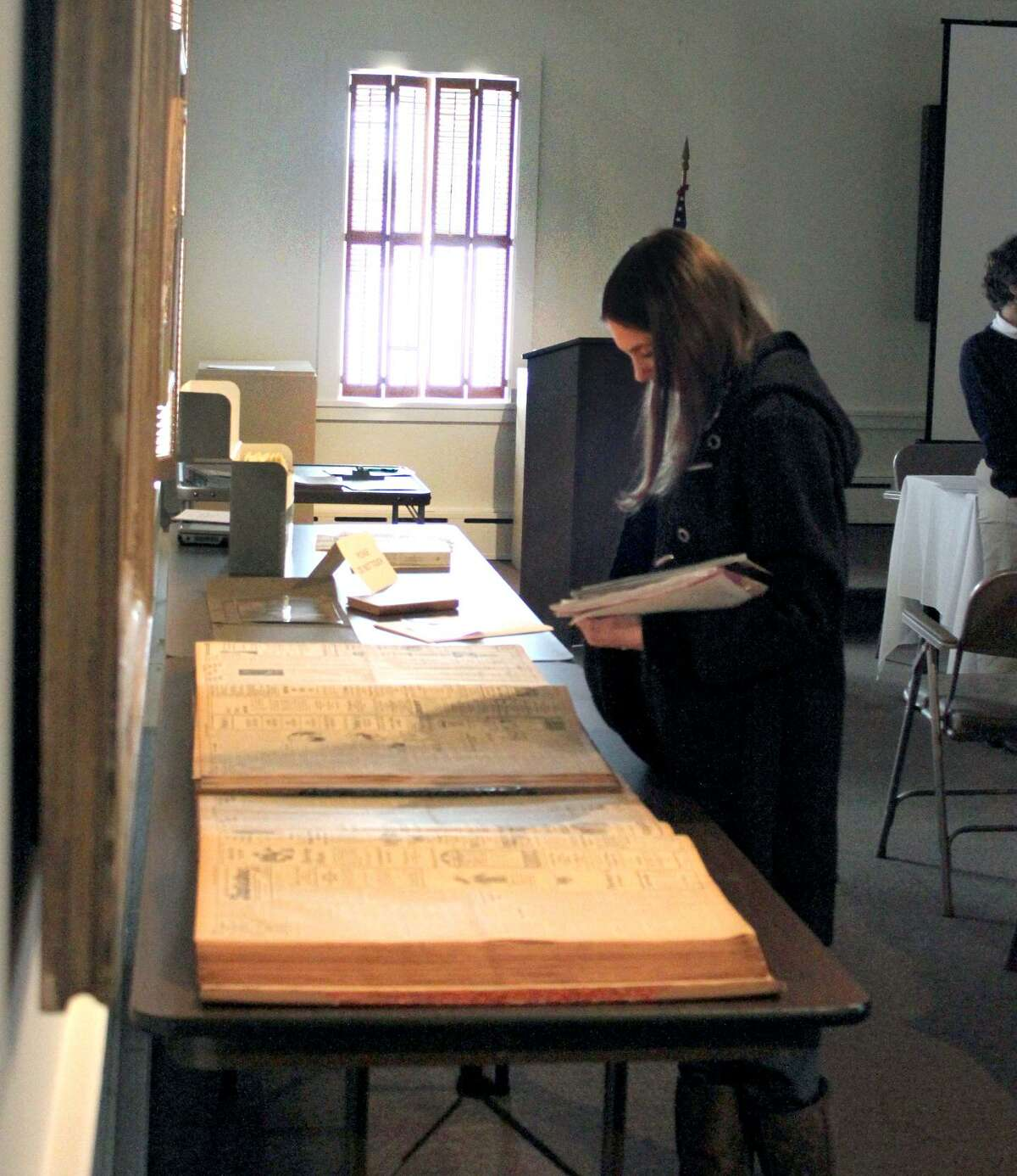 A student visiting the Torrington Historical Society looks over bound copies of vintage newspapers.
