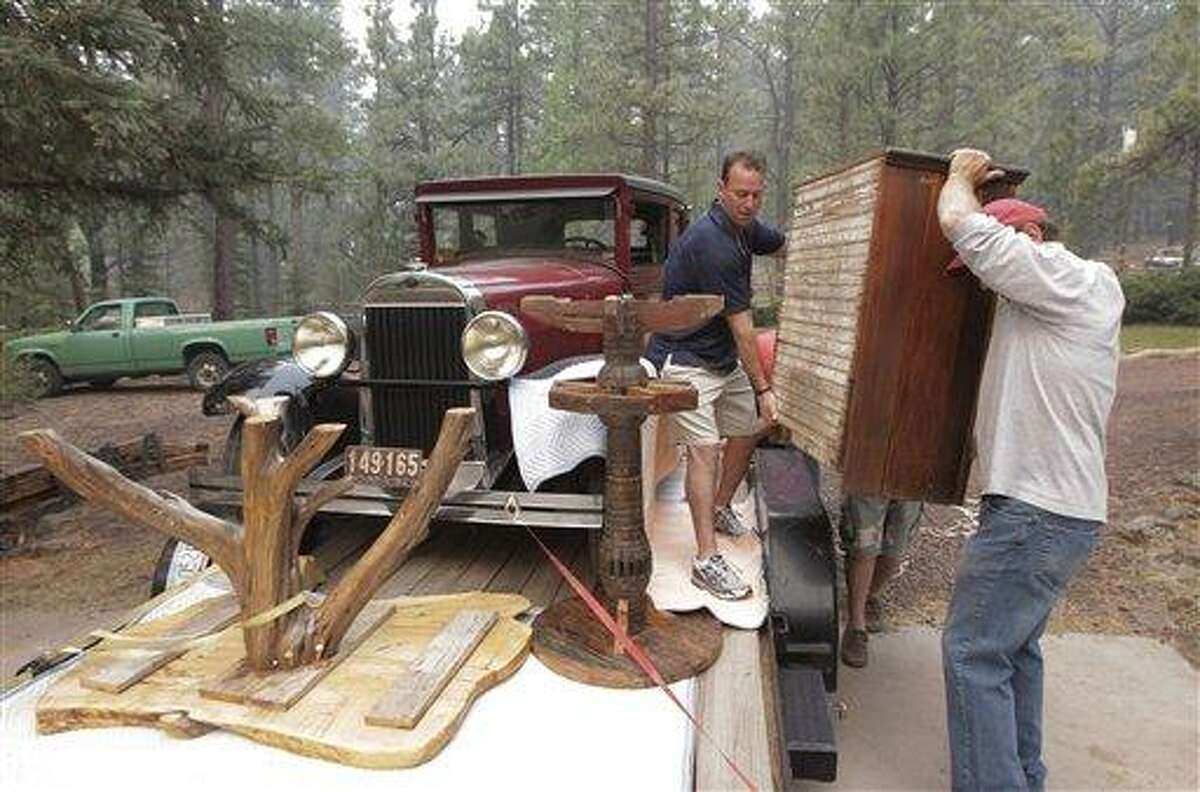 A 1928 Oldsmobile sedan sits in a flatbed trailer as Allan Johnson, right, and Larry Duffy move furniture as they evacuate their home in Greer, Ariz., Sunday, June 5, 2011. Crews used controlled backfires early Sunday to blunt the advance of a major wildfire near mountain communities in eastern Arizona, a blaze termed