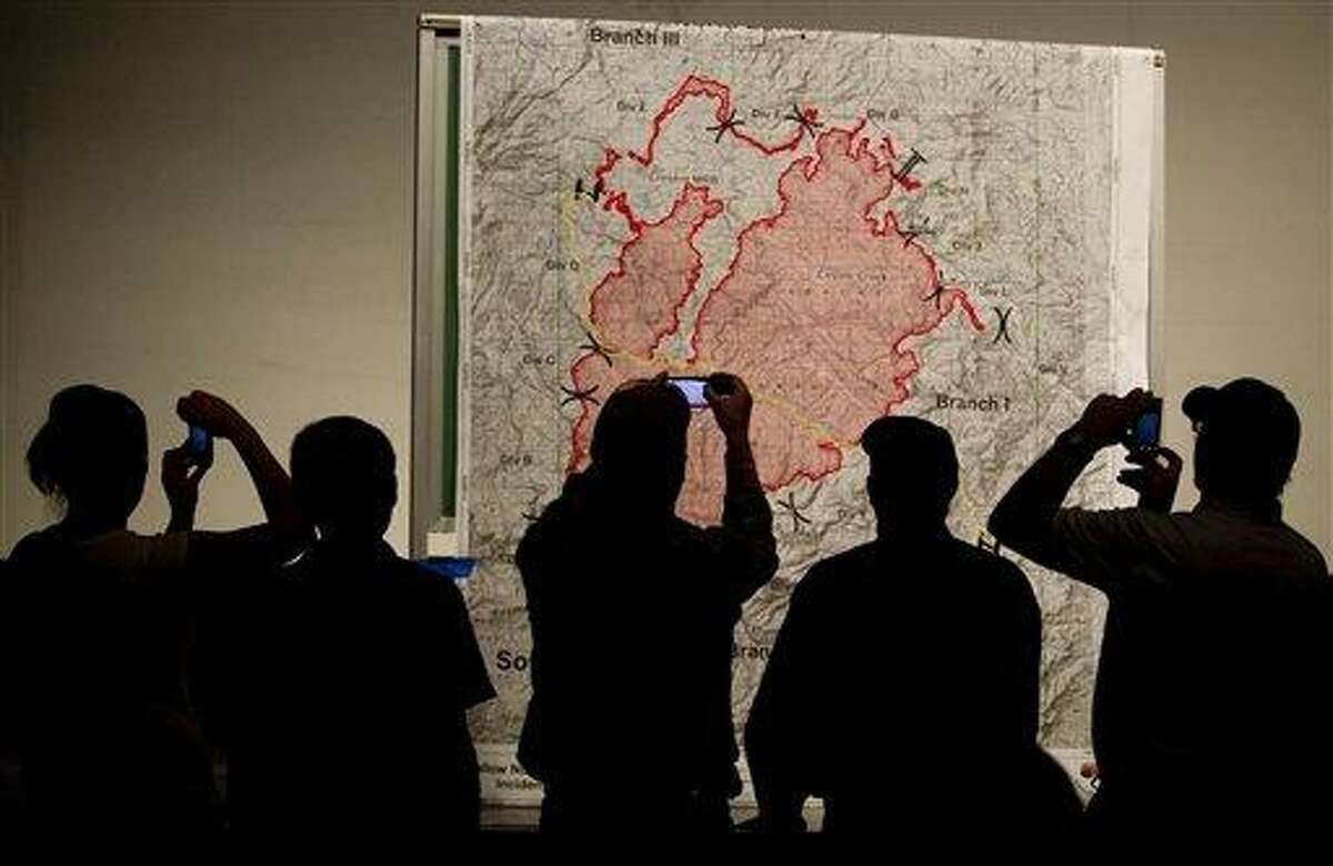 People check out a large map of the Wallow Fire before the start of a community meeting held at Blue Ridge High School Sunday June 5, 2011, in Eager, Ariz. Crews used controlled backfires early Sunday to blunt the advance of a major wildfire near mountain communities in eastern Arizona, a blaze termed