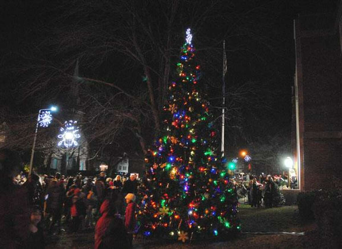 MIKE AGOGLIATI/Register Citizen Residents gather around the tree in Coe Memorial Park Friday night during Torrington's Light Up Main event.