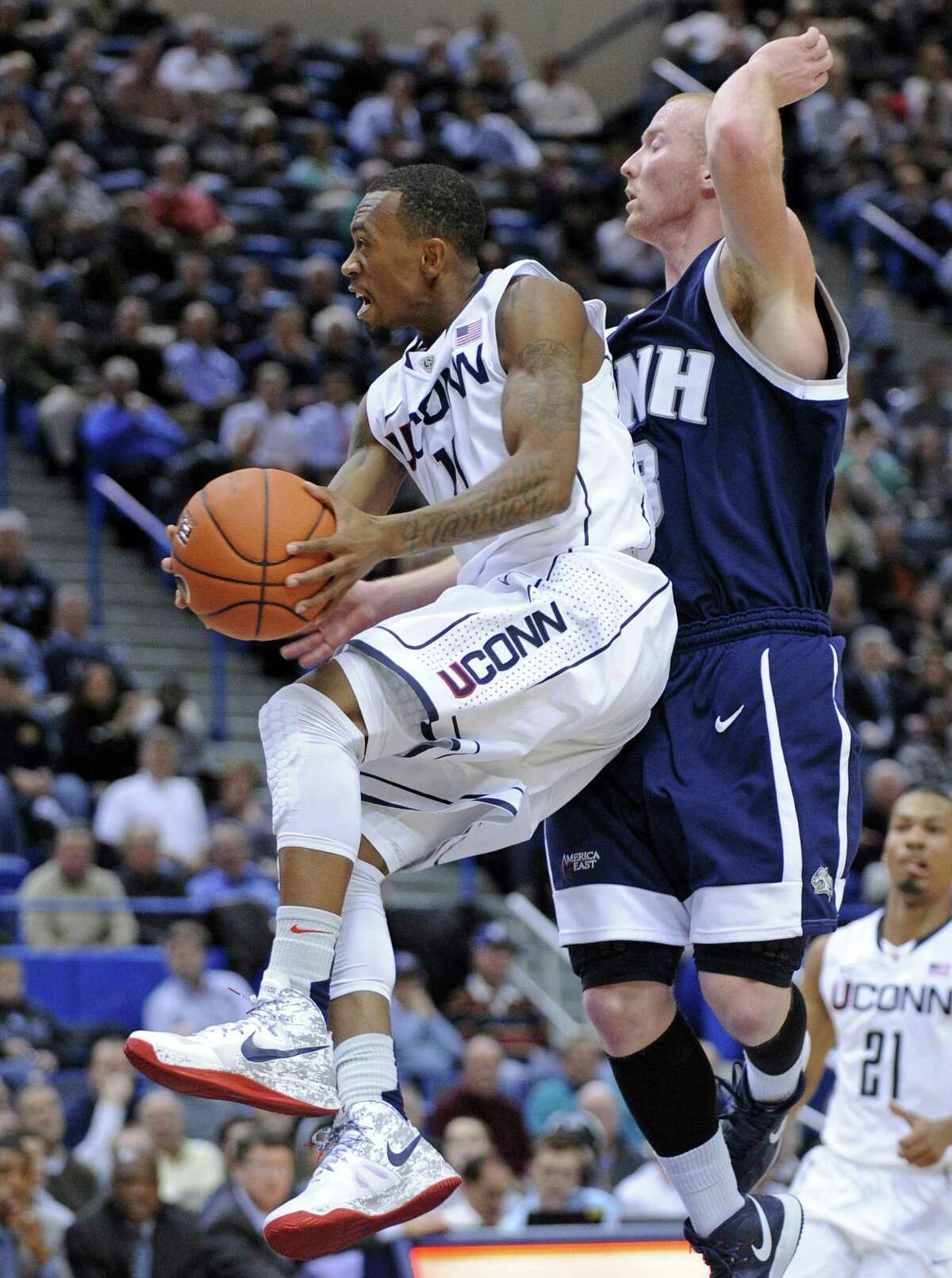Connecticut's Ryan Boatright, left, drives past New Hampshire's Chandler Rhoads during the second half of an NCAA college basketball game in Hartford, Conn., Thursday, Nov. 29, 2012. Boatright scored a team-high 19 points in Connecticut's 61-53 victory. (AP Photo/Fred Beckham)