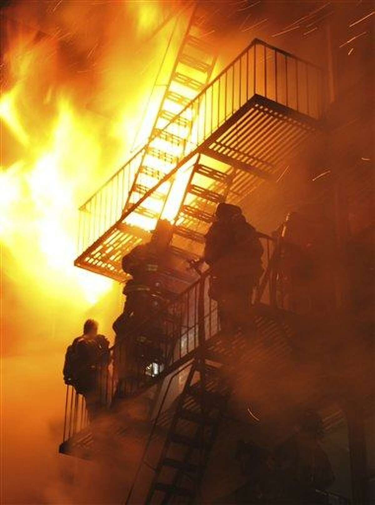 Firefighters stand on the fire escape as winds whip the flames from a five-alarm fire in the Brooklyn borough of New York late Saturday Feb. 19, 2011. Strong winds have meant several hours of work for hundreds of New York City firefighters trying to extinguish a fire that ripped through a six-story apartment building. A fire department spokesman says at least 20 firefighters have been injured while battling Saturday's (AP Photo/Paul Martinka)