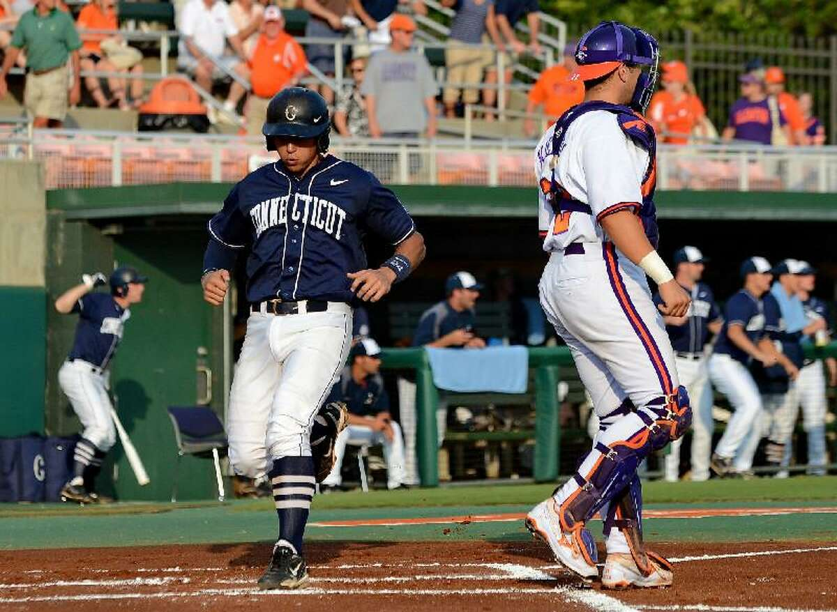 ASSOCIATED PRESS Connecticut's L.J. Mazzilli, left, scores behind Clemson catcher Spencer Kieboom, right, during an NCAA regional tournament game at Doug Kingsmore Stadium Monday in Clemson, S.C. UConn won 14-1 to advance to the Super Regionals against South Carolina this weekend.