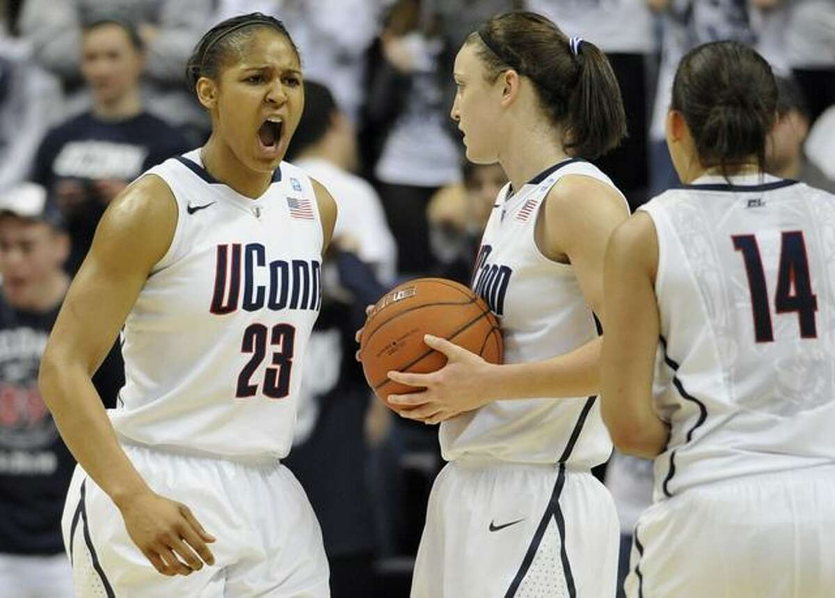Connecticut's Maya Moore, left, reacts to a foul against Connecticut as teamamtes Kelly Faris, center, and Bria Hartley (14) look on, during the second half of an NCAA college basketball game against Notre Dame, in Storrs, Conn., Saturday, Feb. 19, 2011. (AP Photo/Jessica Hill)