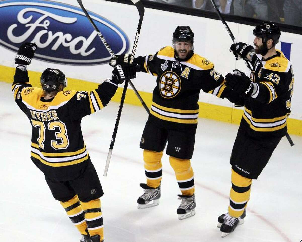 ASSOCIATED PRESS Boston Bruins left wing Mark Recchi, center, celebrates with teammates Michael Ryder, left, and Zdeno Chara after scoring the second goal against the Vancouver Canucks during the second period in Game 3 of the NHL hockey Stanley Cup Finals between the Boston Bruins and the Vancouver Canucks in Boston.