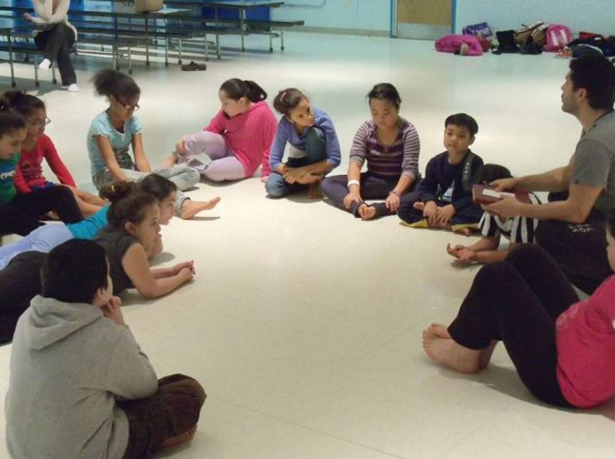 RICKY CAMPBELL/ Register CitizenEdwin Olvera (far right) explains the upcoming performances to the kids in ASAP's dance program. Kids in second through fifth grades in Region 12 and Forbes school are involved