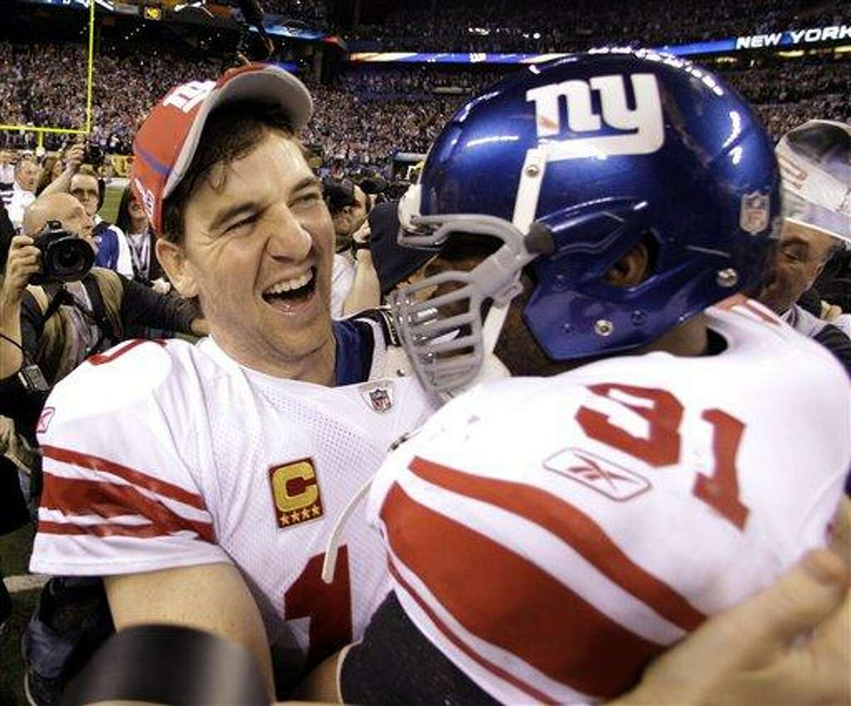 New York Giants quarterback Eli Manning, left, and Aaron Ross celebrate their team's 21-17 win over the New England Patriots in the NFL Super Bowl XLVI football game, Sunday, Feb. 5, 2012, in Indianapolis. (AP Photo/Eric Gay)