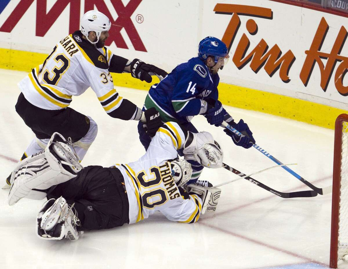 Vancouver Canucks left wing Alex Burrows skates around Boston Bruins defenseman Zdeno Chara and Bruins goalie Tim Thomas on his way to scoring the winning goal during the first overtime period of Game 2 of the NHL hockey Stanley Cup Finals on Saturday, June 4, 2011, in Vancouver, British Columbia. (AP Photo/The Canadian Press, Jonathan Hayward)