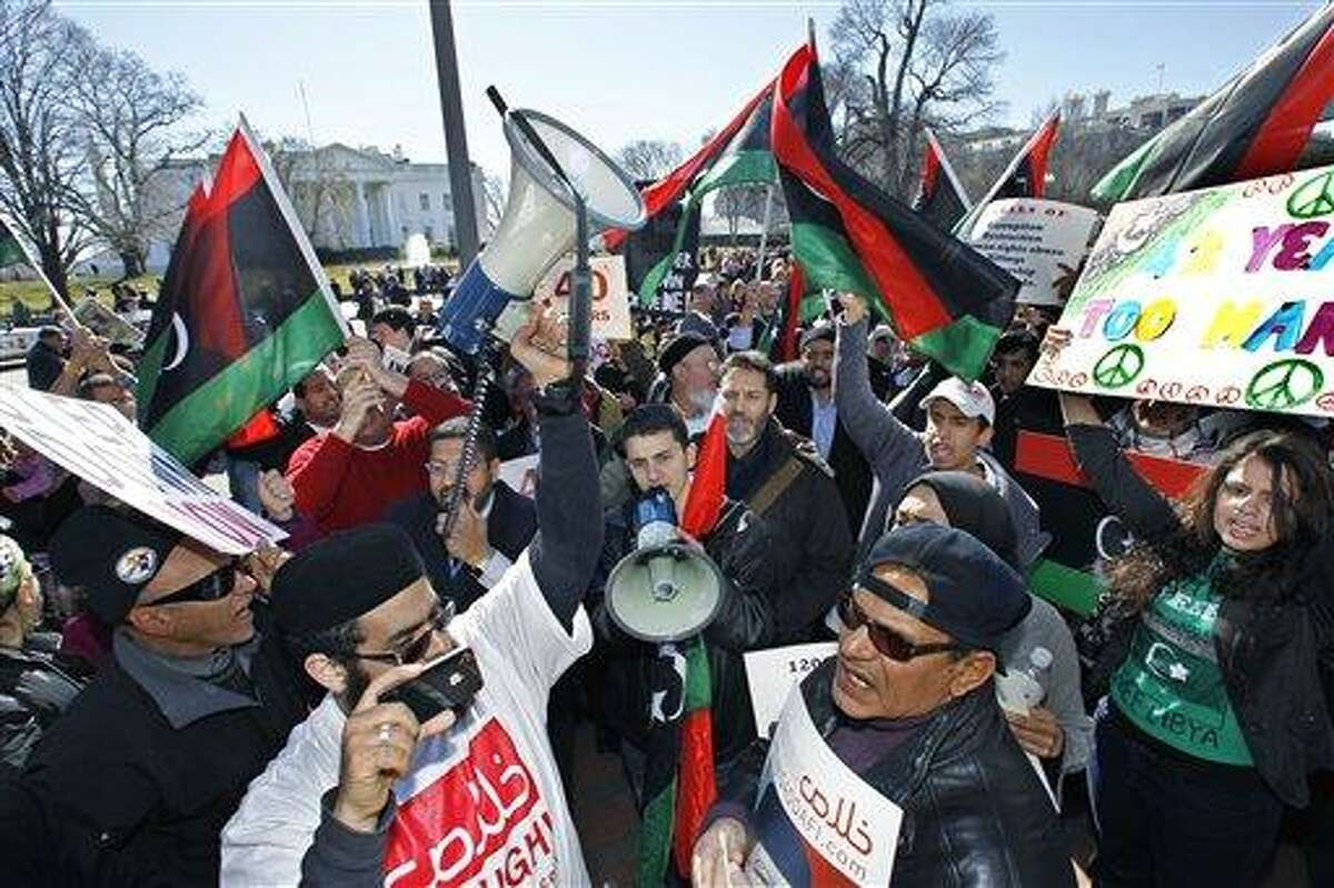 Protestors waving Libyan flags gather in front of the White House in Washington, Saturday, Feb. 19, 2011, call for the ouster of Libyan leader Moammar Gadhafi. Gadhafi's forces fired on mourners leaving a funeral for protesters Saturday in the eastern city of Benghazi, killing at least 15 people and wounding scores more as the regime tried to squelch calls for an end to the ruler's 42-year grip on power. (AP Photo/Manuel Balce Ceneta) Protestors waving Libyan flags gather in front of the White House in Washington, Saturday, Feb. 19, 2011, demanding the ouster of Libyan leader Moammar Gadhafi. (AP Photo/Manuel Balce Ceneta)