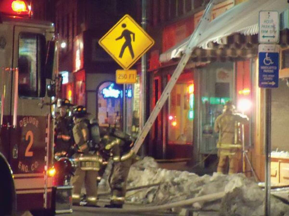 RICKY CAMPBELL/ Register Citizen Winsted firefighters finish extinguishing the blaze at 412 Main St. after oily rags were the alleged cause of the fire.