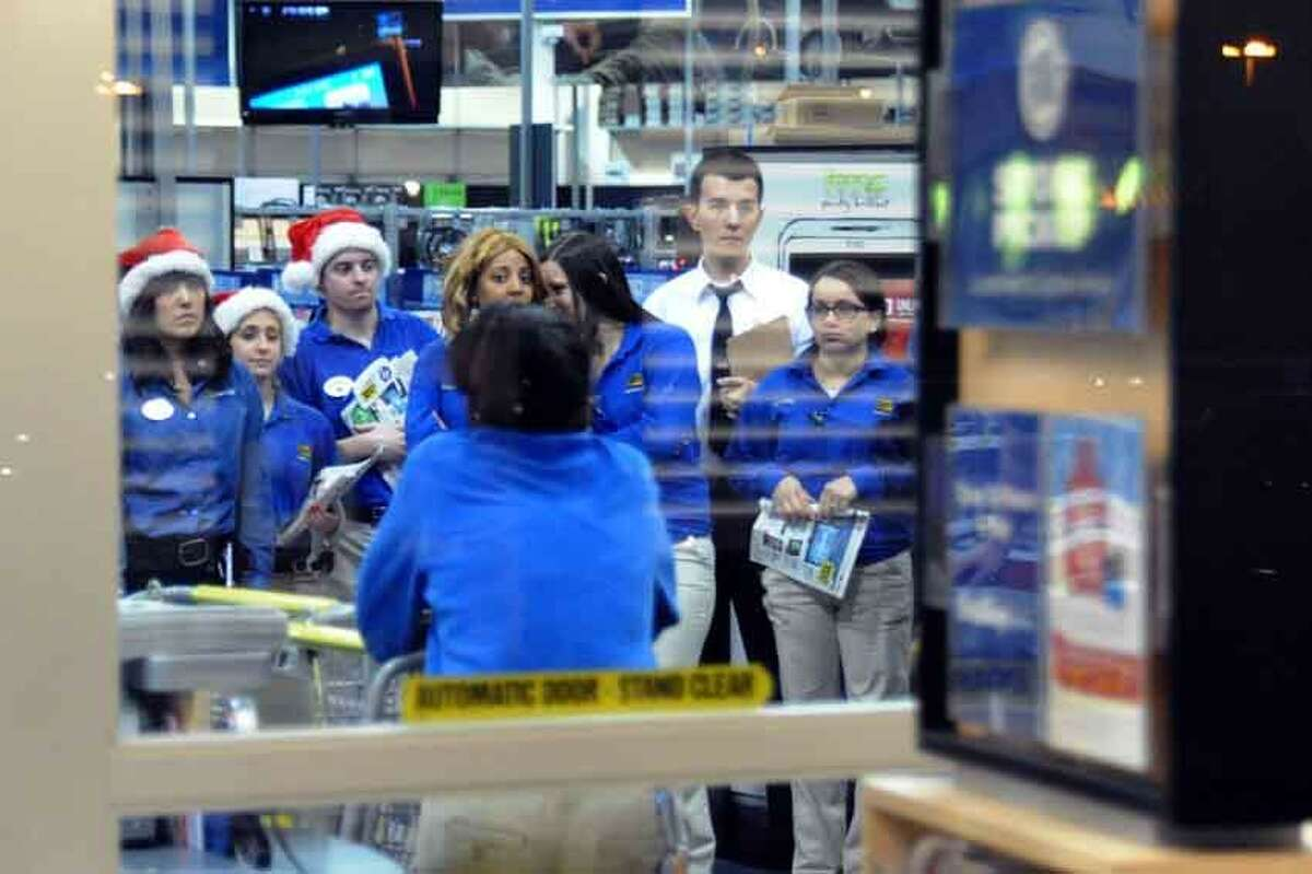 Best Buy employees, circulars in hand, anxiously await the 12:01 a.m. Friday opening, when crowds who were waiting outside would pour into the North Haven store. V.M. Williams/Register