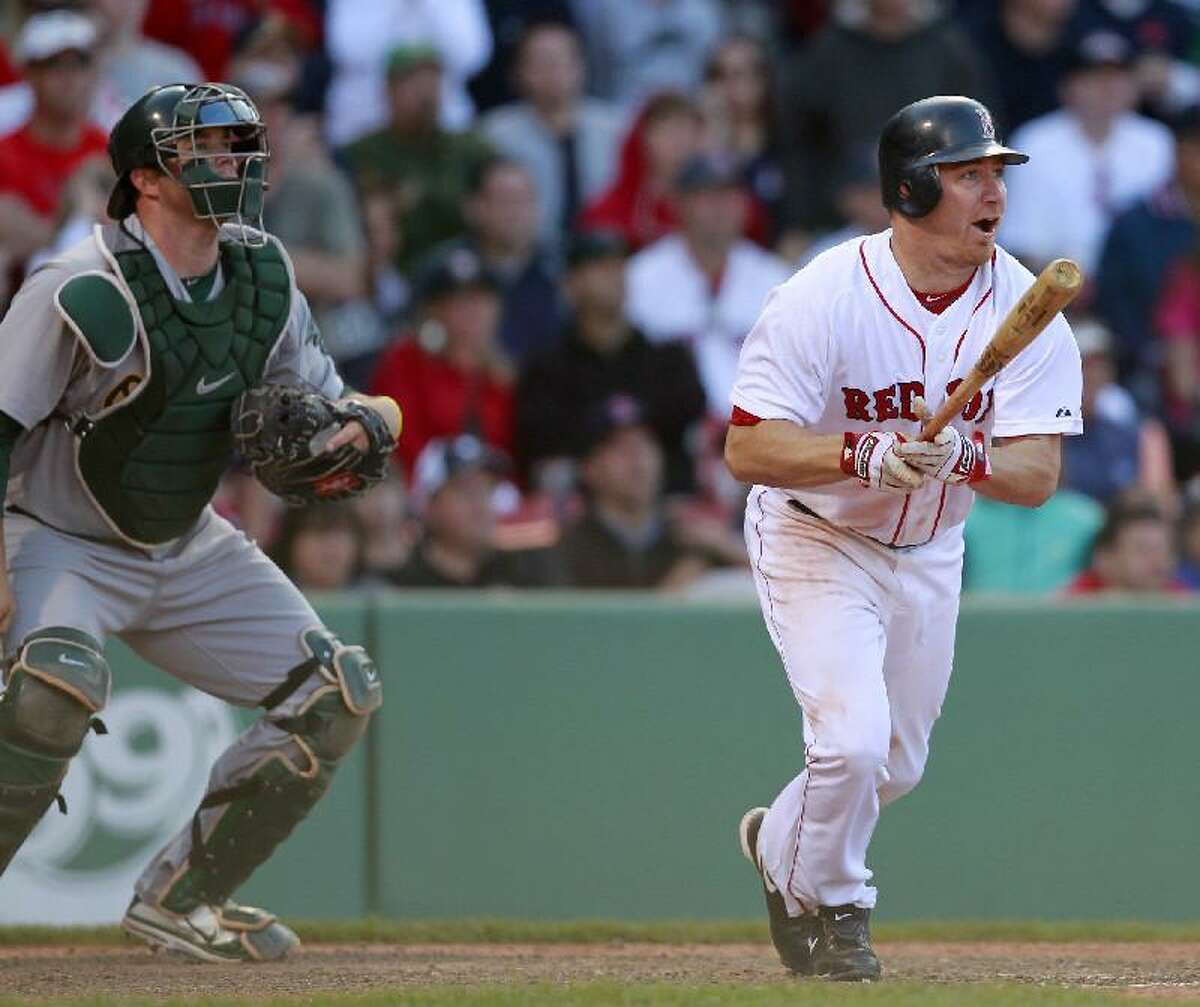 ASSOCIATED PRESS Boston's J.D. Drew, right, watches his game-winning RBI single in front of Oakland catcher Landon Powell in the 14th inning of Saturday's game at Fenway Park in Boston. The Red Sox won 9-8 in 14 innings.