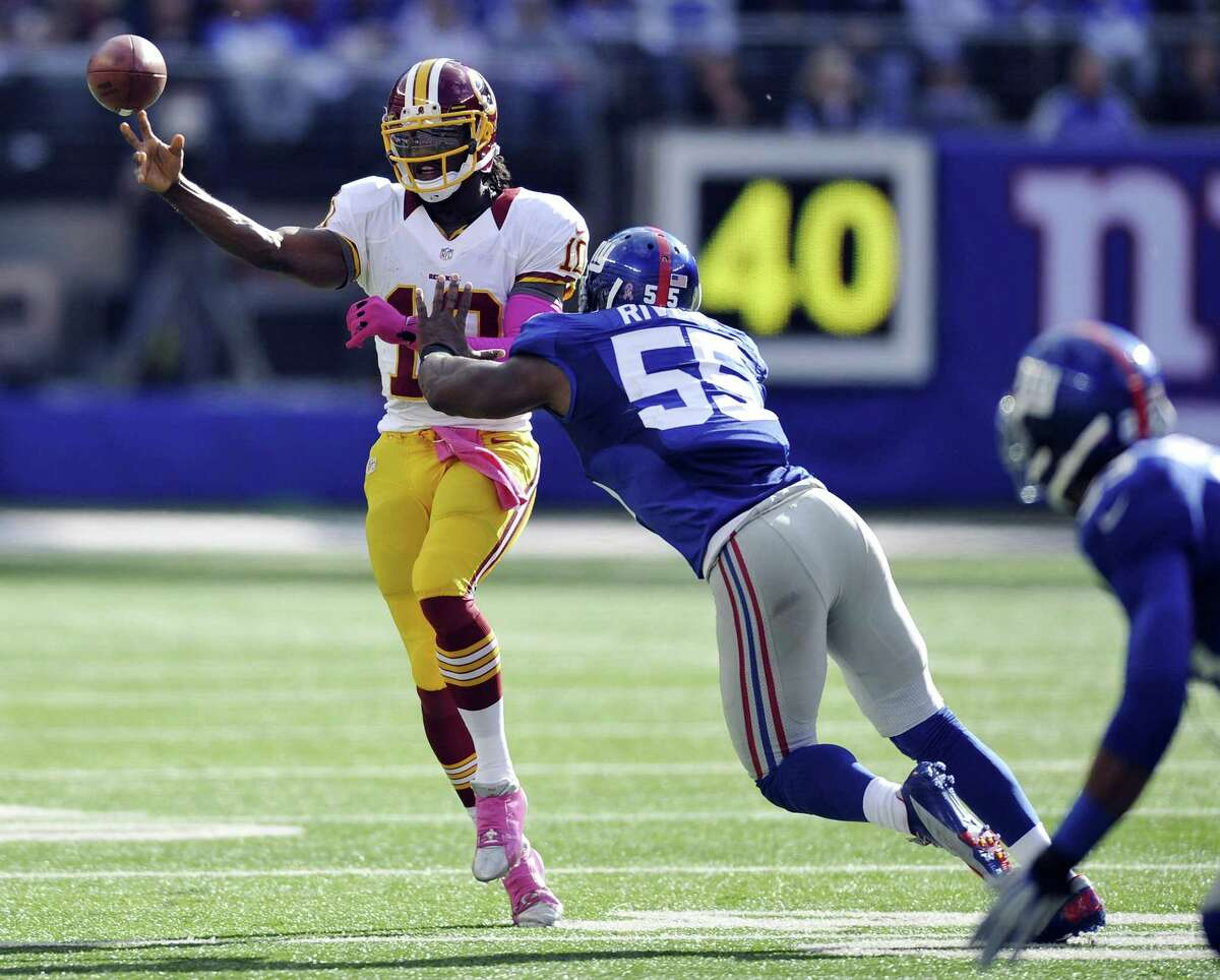 Washington Redskins quarterback Robert Griffin III looks to pass as he is pressured by New York Giants linebacker Keith Rivers (55) during the second half of an NFL football game Sunday, Oct. 21, 2012, in East Rutherford, N.J. (AP Photo/Bill Kostroun)