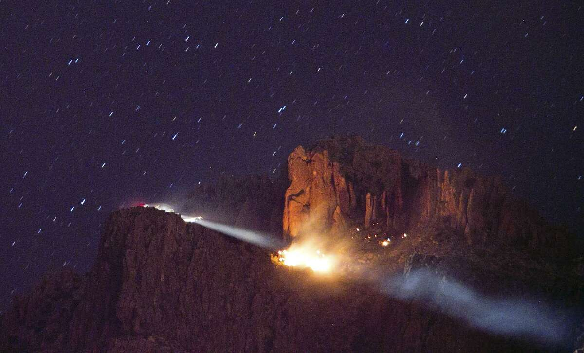 A floodlight, left, is trained on a fire from a small plane crash Wednesday in the Superstition Mountains in Apache Junction, east of Phoenix. Associated Press