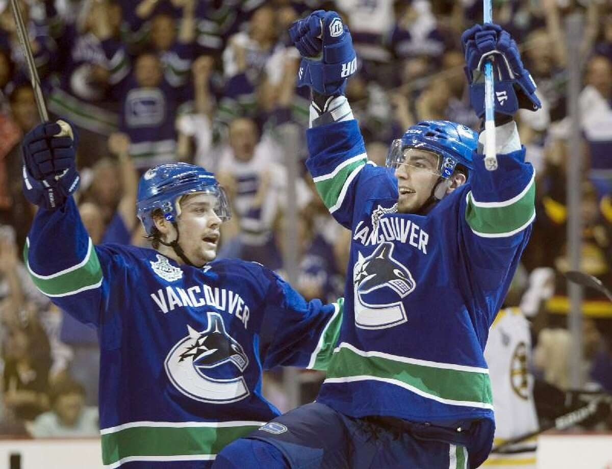 ASSOCIATED PRESS Vancouver Canucks left wing Alex Burrows, right, celebrates with teammate Mason Raymond after scoring the first goal against the Boston Bruins during the first period in Game 2 of the Stanley Cup Finals Saturday in Vancouver, British Columbia.