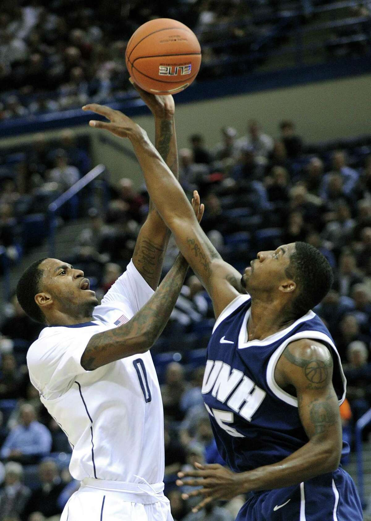 Connecticut's Phillip Nolan, left, shoots over New Hampshire's Ferg Myrick during the first half Thursday. (AP Photo/Fred Beckham)