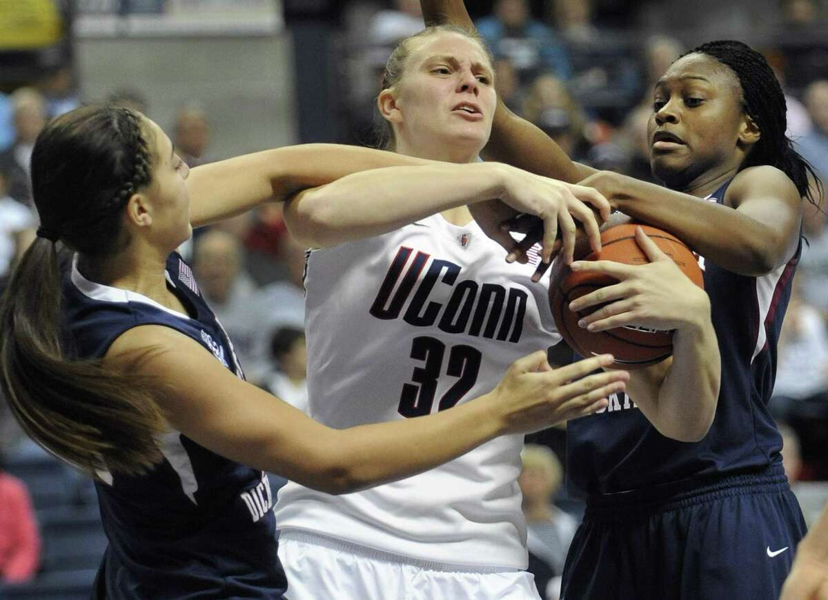 Connecticut's Heather Buck, center, battles for a rebound against Fairleigh Dickinson's Erika Livermore, left, and Erica McKeithan, right, in the second half of an NCAA college basketball game in Storrs, Conn., Friday, Nov. 25, 2011. (AP Photo/Jessica Hill)