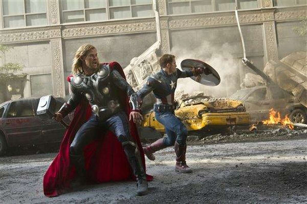 In this film publicity image released by Disney, Chris Hemsworth portrays Thor, left, and and Chris Evans portrays Captain America in a scene from