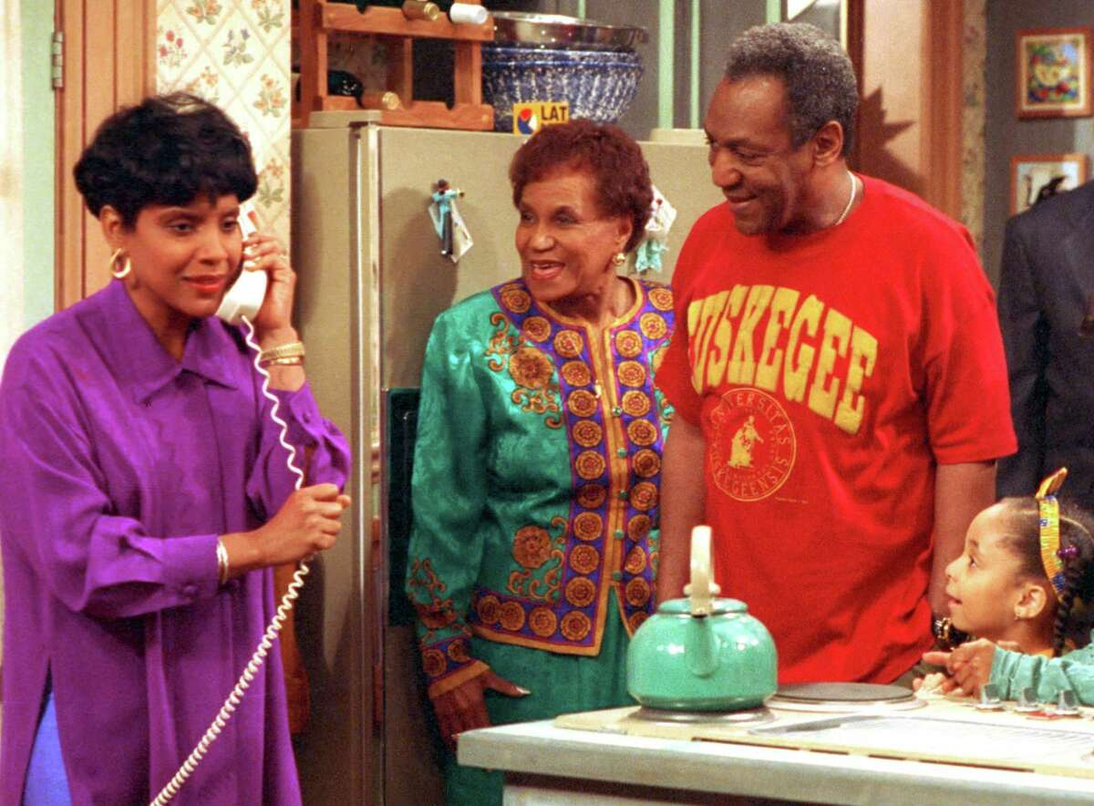 In this 1992 file photo originally released by NBC, Phylicia Rashad, portraying Clair Huxtable, left, talks on the telephone while Clarice Taylor, portraying Anna Huxtable, center, and Bill Cosby, portraying Dr. Cliff Huxtable and Raven Symone portraying Olivia, right, look on in a scene from