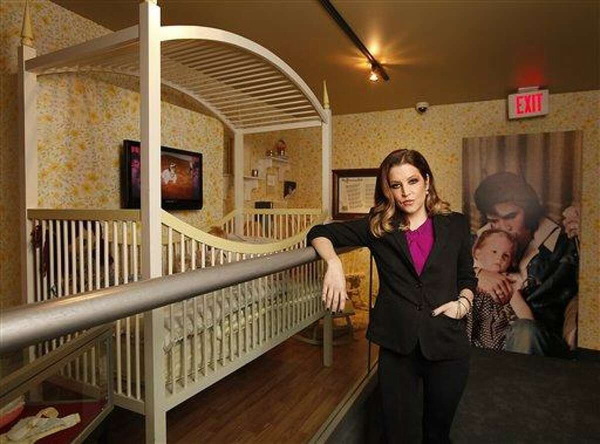 In this Tuesday, Jan. 31, 2012 photo, Lisa Marie Presley stands next to her childhood crib displayed with other mementos in the new exhibit
