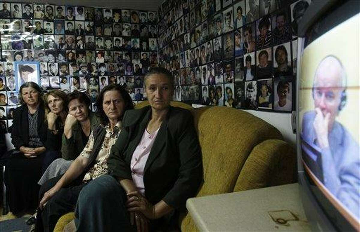 Bosnian Muslim women from Srebrenica, sitting in a room with the walls covered with pictures of victims of the Srebrenica massacre, watch a televised broadcast of former Bosnian Serb military chief Gen. Ratko Mladic's court proceedings at The Hague, Netherlands, in Tuzla, 140 kilometers (87 miles) north of Sarajevo, Bosnia, Friday, June 3, 2011. Mladic told a United Nations war crimes court he is