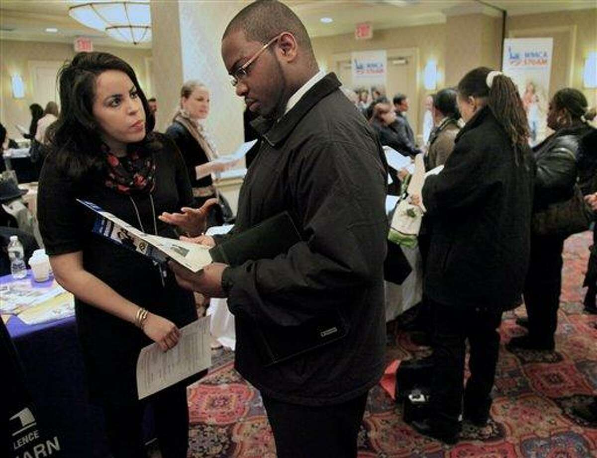 In this Jan. 25 photo, Daniela Silvero, left, an admissions officer at ASA College, discusses job opportunities with Patrick Rosarie, who is seeking a job in IT, during JobEXPO's job fair in New York. The unemployment rate fell for the fifth straight month after a surge of January hiring, a promising shift in the nation's outlook for job growth. Associated Press